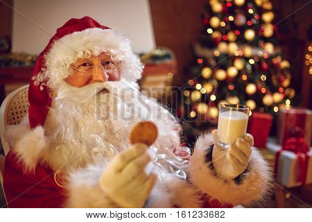 Happy Santa Claus because he found cake under Christmas tree for him