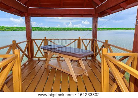 Cayo Coco island, Pullman hotel, Cuba, June 28, 2016, gorgeous amazing closeup view of a wooden made comfortable cozy massage bed inside gazebo against beautiful natural landscape background