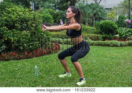 Young female athlete doing squat exercises outdoors in park. Fit girl working out her core and glutes with bodyweight