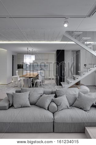 Interior in a modern style with white walls and a stair with metal railing. There is a gray sofa with pillows, kitchen zone with wooden table and chairs, glowing lamps with white lampshades. Vertical.