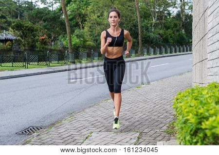 Sport fitness model jogging on sidewalk in quiet city district. Female athlete training outdoors