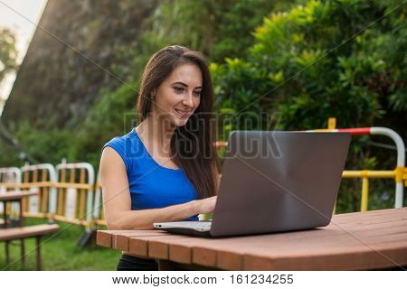 Young pretty smiling student chatting with friends on laptop in the summer park