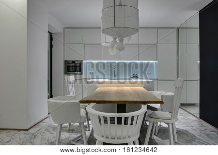 Modern kitchen with white walls and gray tiles with patterns on the floor. There is a wooden table with white chairs, kitchen island with a stove, white lockers, oven, sink with a faucet, mirror.