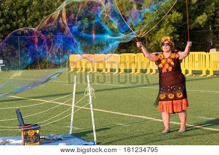 KENNESAW, GA - AUGUST 2016:  A woman uses soapy water to create a huge multi-colored bubble at a festival in Kennesaw GA on August 27 2016.
