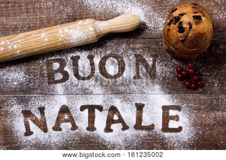high-angle shot of a wooden table sprinkled with icing sugar or flour where you can read the text buon natale, merry christmas in italian, a rolling pin and a small panettone