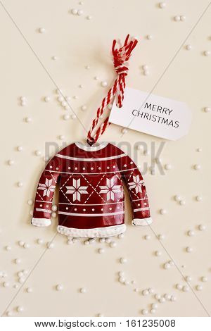 high-angle shot of a christmas ornament with a paper label tied to it with the text merry christmas, placed on an off-white surface sprinkled with small plastic balls simulating snow