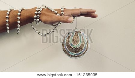 An elegant christmas ball hanging from the hand of a young caucasian man ornamented with a silvery beaded garland