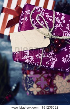 high-angle shot of some cozy christmas gifts wrapped in different nice papers and tied with ribbons and strings of different colors with a blank paper tag tied to one of them