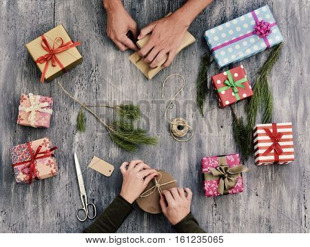 high-angle shot of a young caucasian woman and a young caucasian man wrapping gifts, on a rustic gray wooden table full of gifts and natural twigs and branches