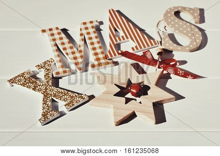 some different patterned letters forming the word xmas and a wooden christmas star, on an off-white surface