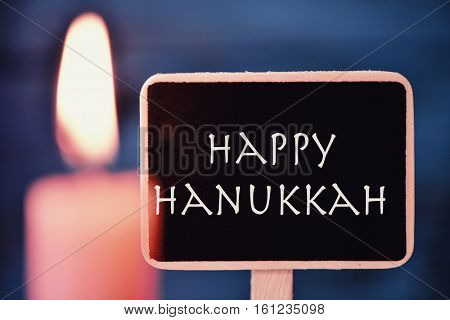 closeup of a black signboard with the text happy Hanukkah, for the Jewish Festival of Lights, and a lit candle