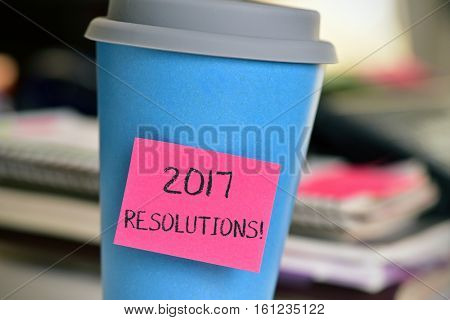 closeup of a pink sticky note with the text 2017 resolutions attached to a blue cup on an office desk