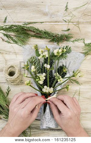 high-angle shot of a young caucasian woman with her fingernails painted red arranging a bunch of mistletoe wrapped in a silvery fabric, on a rustic wooden surface