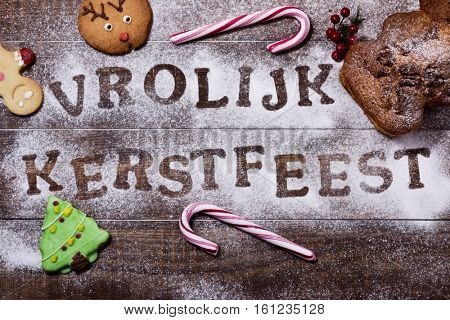 high-angle shot of a wooden table sprinkled with icing sugar or flour where you can read the text vrolijk kerstfeest, merry christmas in dutch, some candy canes and some christmas cookies