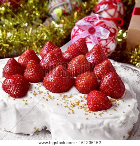 closeup of a heart-shaped cake covered with cream and topped with strawberries, on a table full of gifts and christmas ornaments