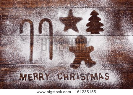 high-angle shot of a wooden table sprinkled with icing sugar or flour where you can read the text merry christmas and the silhouette of some candy canes a gingerbread man, a star and a christmas tree