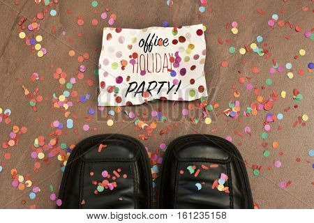 high-angle shot of the feet of a man wearing black leather shoes and a piece of paper with the text office holiday party written in it on the floor all covered with confetti