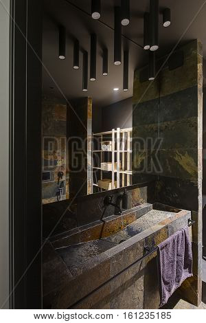 Bathroom in a modern style with the low lighting. It tiled with multi-colored textured tiles. There is a sink with faucet, mirror, violet towel on the holder, wooden shelves with boxes, shower.