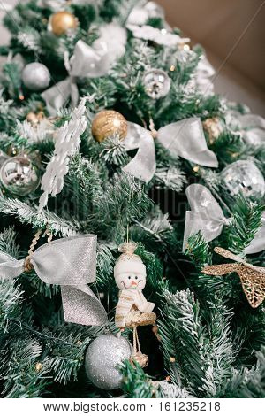Close up of Christmas tree with ornaments baubles, bow, snowflakes, pine cones and lights