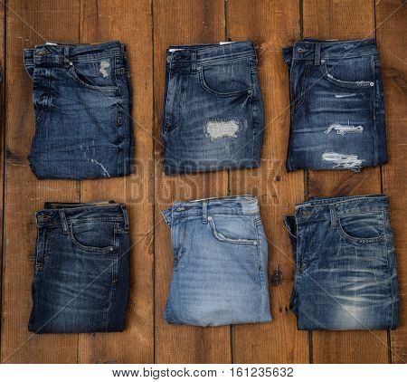 Row of Six blue denim jean â??wooden background