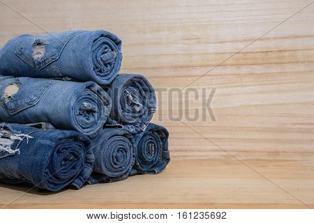 stack of rolls of jeans-wooden board background