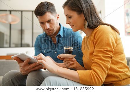 Middle-age couple websurfing on digital tablet at home