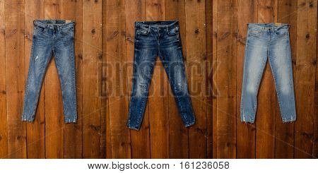Three blue Jeans- wooden background