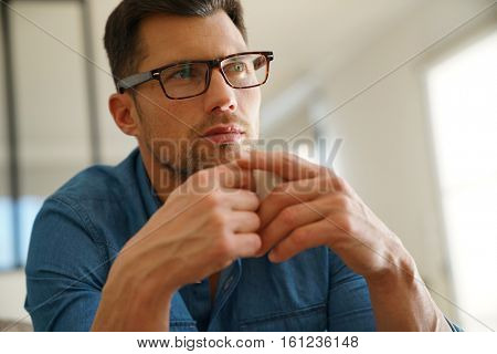 Man with eyeglasses relaxing and drinking coffee at home