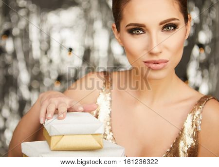 Portrait of a happy woman with gift box and looking at camera over silver background