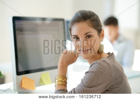 Cheerful startup girl working on desktop computer