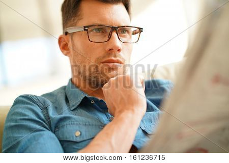 Man relaxing in sofa at home, reading newspaper