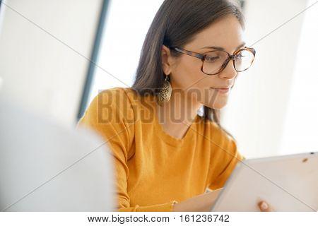 Portrait of trendy girl with eyeglasses websurfing on digital tablet