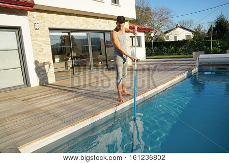 Man cleaning swimming-pool