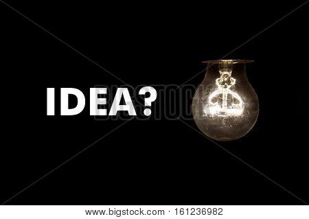 Bulb with message IDEA? on black background