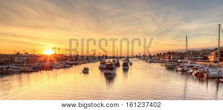Balboa Island harbor at sunset with ships and sailboats visible from the bridge that leads into Balboa Island, Southern California, USA
