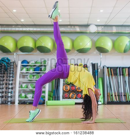 Beautiful young fit woman in sportswear doing yoga pose in gym, one-legged Upward Bow or Wheel Posture