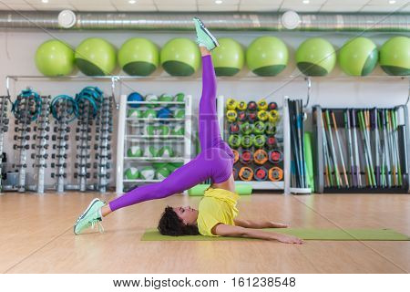 Young athletic woman in sportswear practicing yoga in gym or studio, doing shoulderstand posture, working on balance. Full length, side view.