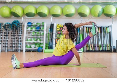 Attractive sportswoman doing yoga exercise in gym or studio, stretching hamstring muscles