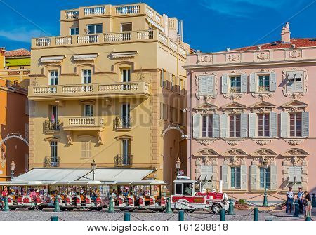 Monaco Ville Monaco - October 7 2016: Red and white trackless train of Monaco front of the princial palace with tourists. The Palace Square or Place du Palais is among most popular destinations in Monaco