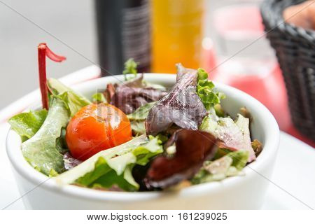 Delicious fresh salad with tomatoes, lettuce, eggplant, zucchini, cheese, parma ham and olive oil.