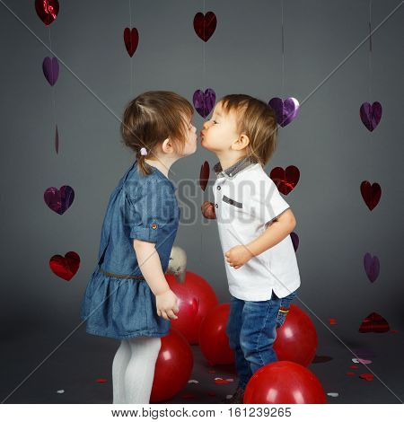 Portrait of two cute adorable baby children toddlers kissing each other in studio with red hearts and balloons on grey background love friendship childhood Valentine concept best friends forever