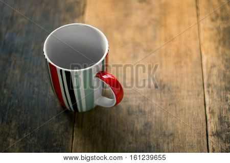 Striped cup white inside on wooden background
