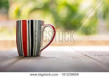 Striped cup on wooden background with ray of light