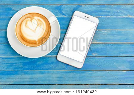 Top View Hot Latte Coffee In White Cup And Smartphone With Blank Screen On Blue Vintage Wooden Table