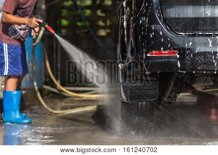 A Man Spraying Pressure Washer For Car Wash In Car Care Shop