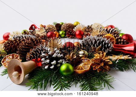 Christmas decoration with glass and wooden jingle bells. Christmas greeting background with red ornaments decorated wreath.