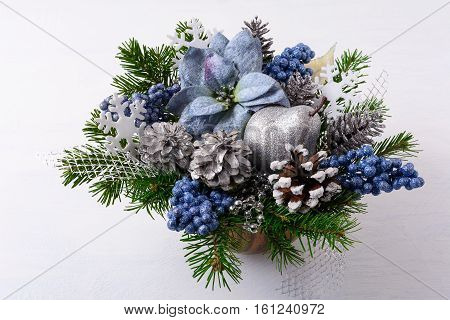 Christmas greenery with silver glitter decor and blue silk poinsettias. Artificial Christmas flower arrangement with pine cones and fir branches. Christmas table centerpiece.