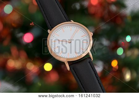 Black leather strap wrist watch in Christmas time in front of Christmas tree lights background
