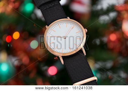 Wrist watch with black nylon strap in Christmas time in front of Christmas tree lights background