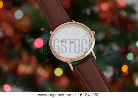 Brawn leather strap wrist watch in Christmas time in front of Christmas tree lights background